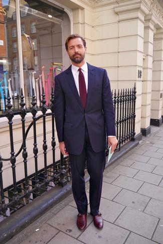 Patrick Grant trägt dunkelblauer Anzug, weißes Businesshemd, dunkelrote Monks aus Leder, dunkelrote Krawatte