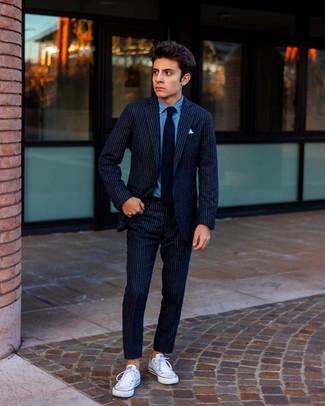 Wie kombinieren: dunkelblauer vertikal gestreifter Wollanzug, blaues Jeanshemd, weiße Segeltuch niedrige Sneakers, schwarze Krawatte