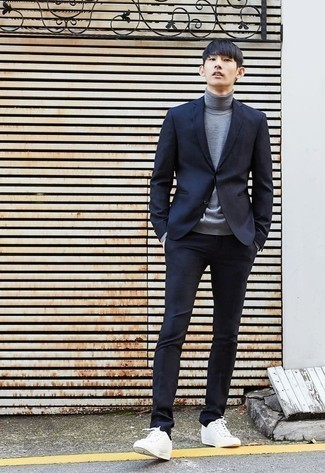 Grauen Rollkragenpullover kombinieren: trends 2020: Paaren Sie einen grauen Rollkragenpullover mit einem dunkelblauen Anzug für eine klassischen und verfeinerte Silhouette. Suchen Sie nach leichtem Schuhwerk? Entscheiden Sie sich für weißen Segeltuch niedrige Sneakers für den Tag.