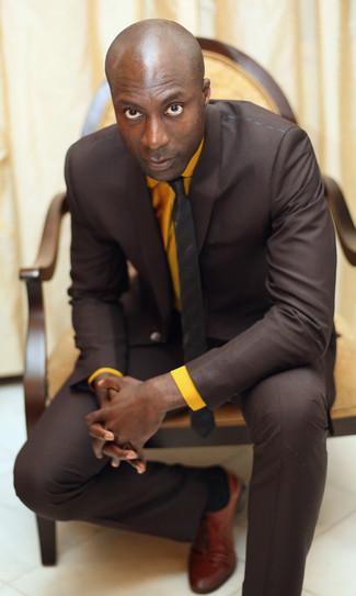 Dermot O'Leary trägt Dunkelbrauner Anzug, Orange Businesshemd, Rotbraune Leder Oxford Schuhe, Dunkelbraune vertikal gestreifte Krawatte