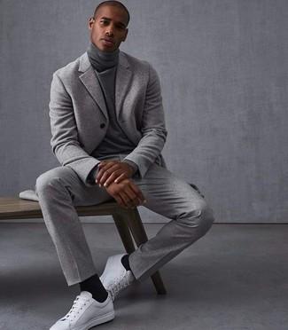 Wie kombinieren: grauer Wollanzug, grauer Rollkragenpullover, weiße Leder niedrige Sneakers, schwarze Socke