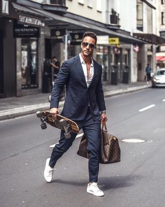 Wie kombinieren: dunkelblauer Anzug, weißes Langarmhemd, weiße Leder niedrige Sneakers, dunkelbraune bedruckte Leder Reisetasche