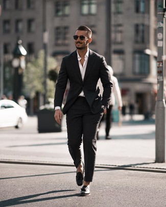 Wie kombinieren: schwarzer Anzug, weißes Langarmhemd, schwarze Leder Slipper mit Quasten, schwarze Sonnenbrille