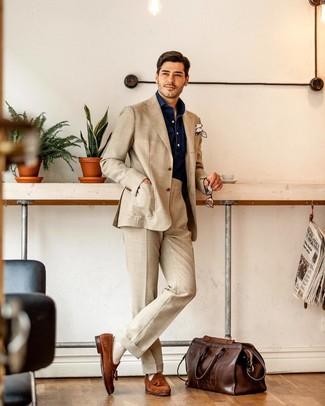 Wie kombinieren: hellbeige Anzug, dunkelblaues Chambray Langarmhemd, rotbraune Wildleder Slipper mit Quasten, dunkelbraune Leder Reisetasche