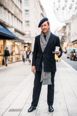 Wie kombinieren: schwarzer vertikal gestreifter Anzug, schwarzer Pullover mit einem Rundhalsausschnitt, schwarze Leder Slipper, weißer und schwarzer Schal mit Hahnentritt-Muster