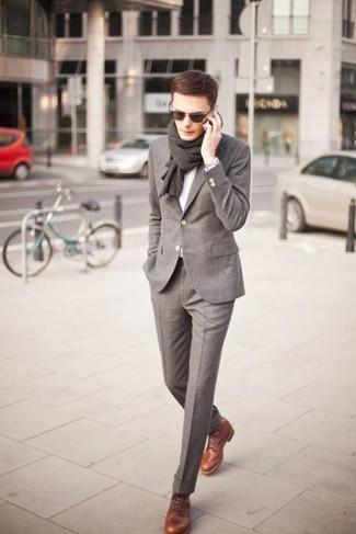 Wie kombinieren: grauer Wollanzug, grauer Pullover mit einem V-Ausschnitt, braune Lederformelle stiefel, dunkelbrauner Schal