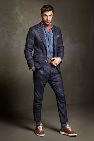 Wie kombinieren: dunkelblauer vertikal gestreifter Anzug, orange Rollkragenpullover, blaues Jeanshemd, braune Leder niedrige Sneakers