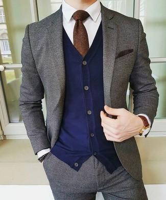 Wie kombinieren: grauer Wollanzug, dunkelblaue Strickjacke, weißes Businesshemd, dunkelbraune Krawatte