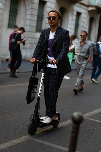 Wie kombinieren: schwarzer vertikal gestreifter Anzug, weißes bedrucktes T-Shirt mit einem Rundhalsausschnitt, weiße Leder niedrige Sneakers, schwarze bedruckte Shopper Tasche aus Segeltuch