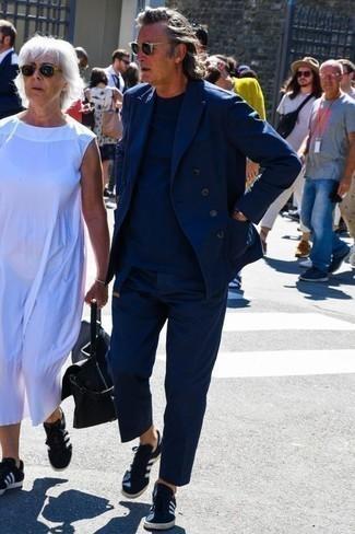 Dunkelblauen Anzug kombinieren: trends 2020: Stechen Sie unter anderen modebewussten Menschen hervor mit einem dunkelblauen Anzug und einem dunkelblauen T-Shirt mit einem Rundhalsausschnitt. Fühlen Sie sich mutig? Vervollständigen Sie Ihr Outfit mit dunkelblauen und weißen Segeltuch niedrigen Sneakers.