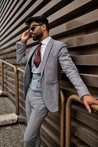 Wie kombinieren: grauer vertikal gestreifter Anzug, graue Weste, weißes Businesshemd, dunkelrote bedruckte Krawatte