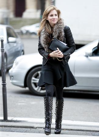 Wie kombinieren: schwarze gesteppte Leder Bikerjacke, schwarzes ausgestelltes Kleid mit Rüschen, schwarze kniehohe Stiefel aus Leder, schwarze Leder Clutch