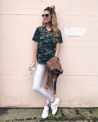 Wie kombinieren: braune Wildleder Bikerjacke, dunkelgrünes Camouflage T-Shirt mit einem V-Ausschnitt, weiße enge Jeans, weiße Leder niedrige Sneakers
