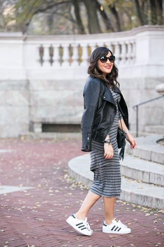 Wie kombinieren: schwarze gesteppte Leder Bikerjacke, graues horizontal gestreiftes figurbetontes Kleid, weiße und schwarze Leder niedrige Sneakers, schwarze Leder Umhängetasche