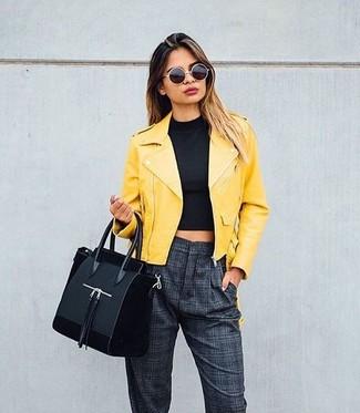Wie kombinieren: gelbe Leder Bikerjacke, schwarzes kurzes Oberteil, dunkelgraue Karottenhose mit Karomuster, schwarze Shopper Tasche aus Wildleder