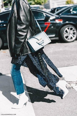 Wie kombinieren: schwarze Leder Bikerjacke, dunkelblaues gepunktetes Midikleid, blaue Jeans, weiße Leder Stiefeletten