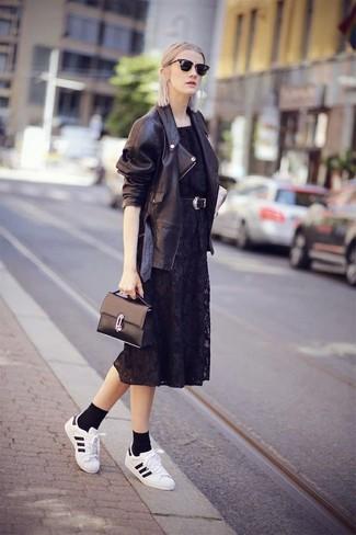 Wie kombinieren: schwarze Leder Bikerjacke, schwarzes Midikleid aus Spitze, weiße und schwarze Leder niedrige Sneakers, schwarze Satchel-Tasche aus Leder