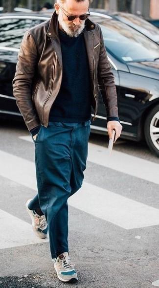 Wie kombinieren: braune Leder Bikerjacke, schwarzer Pullover mit einem Rundhalsausschnitt, dunkelblaue Chinohose, hellbeige Wildleder Sportschuhe