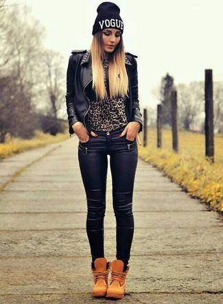 Wie kombinieren: schwarze beschlagene Leder Bikerjacke, brauner Pullover mit einem Rundhalsausschnitt mit Leopardenmuster, schwarze Leder enge Jeans, beige Nubuk flache Stiefel mit einer Schnürung