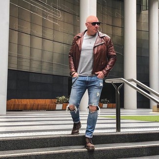 Wie kombinieren: braune Leder Bikerjacke, grauer Pullover mit einem Rundhalsausschnitt, blaue Jeans mit Destroyed-Effekten, braune Lederfreizeitstiefel