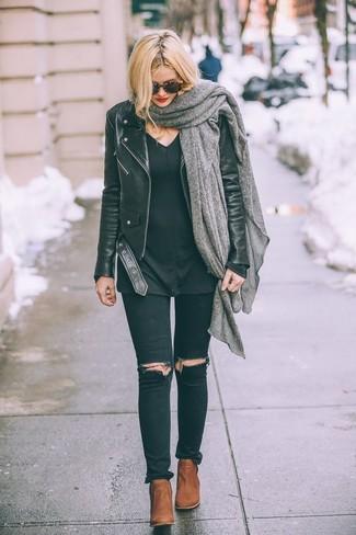 Wie kombinieren: schwarze Leder Bikerjacke, schwarzer Pullover mit einem V-Ausschnitt, schwarze enge Jeans mit Destroyed-Effekten, rotbraune Leder Stiefeletten