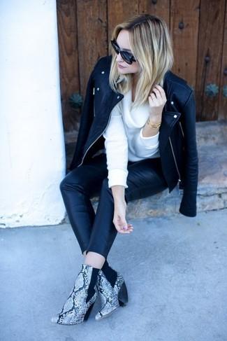 Wie kombinieren: schwarze Leder Bikerjacke, weißer Pullover mit einer weiten Rollkragen, schwarze enge Hose aus Leder, graue Leder Stiefeletten mit Schlangenmuster
