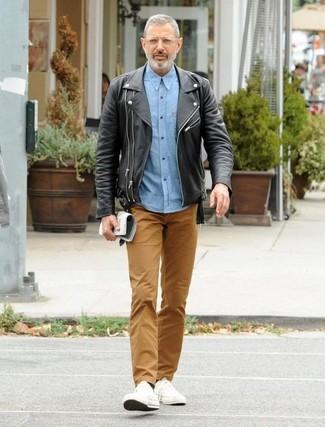 Wie kombinieren: schwarze Leder Bikerjacke, hellblaues Chambray Langarmhemd, braune Chinohose, weiße Segeltuch niedrige Sneakers