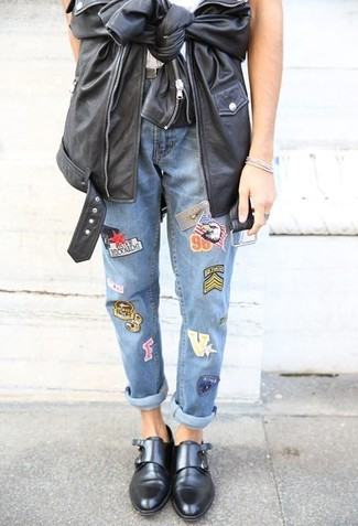 Wie kombinieren: schwarze Leder Bikerjacke, weißes T-Shirt mit einem Rundhalsausschnitt, blaue bestickte Jeans, schwarze Doppelmonks aus Leder