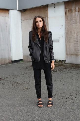 Wie kombinieren: schwarze Leder Bikerjacke, schwarze Tunika, schwarze Chinohose, schwarze flache Sandalen aus Leder