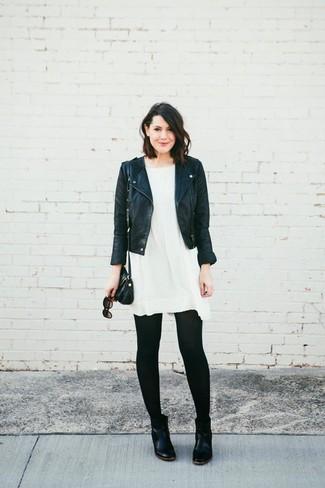 Wie kombinieren: schwarze Leder Bikerjacke, weißes schwingendes Kleid, schwarze Chelsea-Stiefel aus Leder, schwarze Leder Umhängetasche