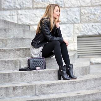 Tragen Sie eine schwarze Leder Bikerjacke und ein graues schwingendes Kleid für ein großartiges Wochenend-Outfit. Schwarze Leder Stiefeletten bringen Eleganz zu einem ansonsten schlichten Look.