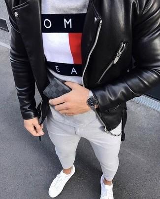 Wie kombinieren: schwarze Leder Bikerjacke, graues bedrucktes T-Shirt mit einem Rundhalsausschnitt, graue enge Jeans, weiße Leder niedrige Sneakers