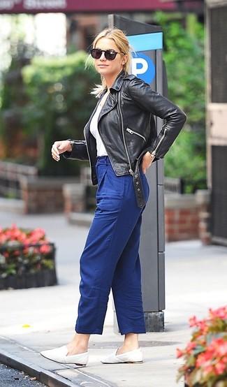 Wie kombinieren: schwarze Leder Bikerjacke, weißes T-Shirt mit einem V-Ausschnitt, blaue Karottenhose, weiße Leder Slipper