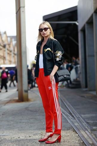 Schwarze bestickte Bikerjacke kombinieren – 4 Damen Outfits: Durch diese Kombi aus einer schwarzen bestickten Bikerjacke und einer roten Jogginghose können Sie Ihrem Wochenend-Stil eine persönliche Note verleihen und immer wieder neue Looks zusammenstellen. Komplettieren Sie Ihr Outfit mit roten Leder Pumps.