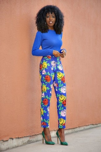 Wie kombinieren: blauer Pullover mit einem Rundhalsausschnitt, blaue Karottenhose mit Blumenmuster, grüne Wildleder Pumps