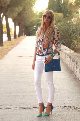 Wie kombinieren: weiße Bluse mit Knöpfen mit Blumenmuster, weiße enge Jeans, blaue Wildleder Sandaletten, blaue Leder Umhängetasche