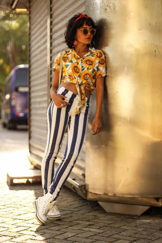 Wie kombinieren: gelbe Bluse mit Knöpfen mit Blumenmuster, weiße und dunkelblaue vertikal gestreifte enge Jeans, weiße hohe Sneakers, rotes Haarband