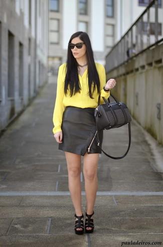 Wie kombinieren: gelbe Seidebluse mit knöpfen, schwarzer Leder Minirock, schwarze Leder Sandaletten, schwarze verzierte Lederhandtasche