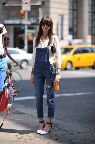 Wie kombinieren: weiße Bluse mit Knöpfen, blaue Jeans Latzhose, weiße und schwarze Leder Pumps, schwarze Wildleder Clutch