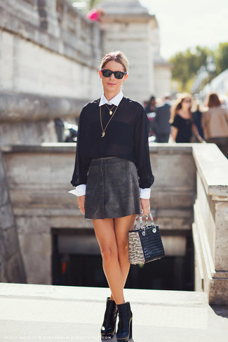 Eine Schwarze und weiße Bluse mit Knöpfen und ein Schwarzer Lederrock mit knöpfen vermitteln eine sorglose und entspannte Atmosphäre. Setzen Sie bei den Schuhen auf die klassische Variante mit Schwarzen Leder Stiefeletten.