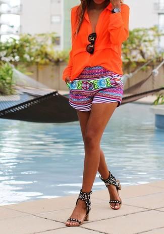 Wie kombinieren: orange Bluse mit Knöpfen, mehrfarbige Shorts mit Blumenmuster, schwarze beschlagene Leder Sandaletten, schwarze Sonnenbrille