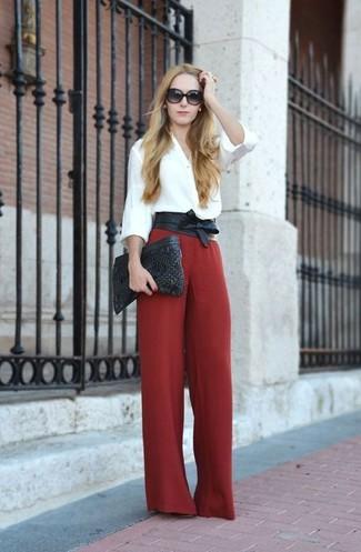 Wie kombinieren: weiße Bluse mit Knöpfen, rote weite Hose, schwarze gesteppte Leder Clutch, schwarzer Leder Taillengürtel