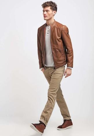 Wie kombinieren: braune Leder Bomberjacke, hellbeige Langarmshirt mit einer Knopfleiste, beige Jeans, braune hohe Sneakers aus Leder