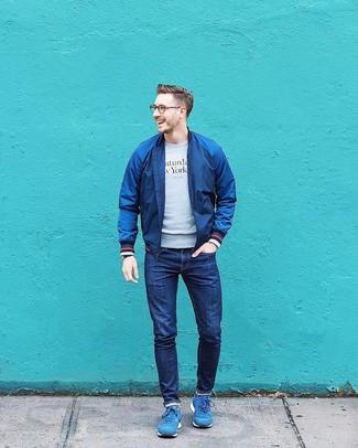 Wie kombinieren: dunkelblaue Bomberjacke, graues bedrucktes Sweatshirt, dunkelblaue Jeans, blaue Sportschuhe