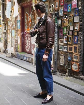 Wie kombinieren: dunkelbraune Leder Bomberjacke, hellblaues Langarmhemd, blaue Jeans, dunkellila Leder Slipper