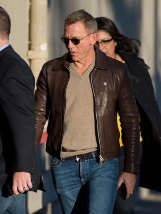 Daniel Craig trägt Dunkelbraune Leder Bomberjacke, Beige Pullover mit V-Ausschnitt, Dunkelblaue Jeans, Schwarzer geflochtener Ledergürtel