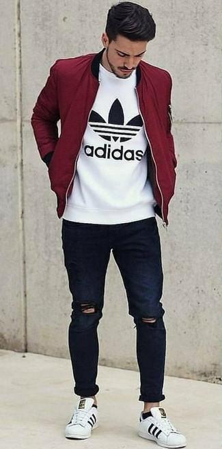 Wie kombinieren: dunkelrote Bomberjacke, weißes und schwarzes bedrucktes T-Shirt mit einem Rundhalsausschnitt, dunkelblaue enge Jeans mit Destroyed-Effekten, weiße Leder niedrige Sneakers