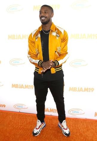 Wie kombinieren: gelbe Satin Bomberjacke, schwarzes T-Shirt mit einem Rundhalsausschnitt, schwarze Jogginghose, mehrfarbige Sportschuhe