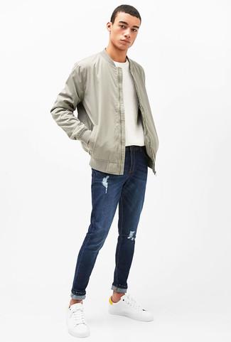 Wie kombinieren: graue Bomberjacke, weißer Pullover mit einem Rundhalsausschnitt, dunkelblaue Jeans mit Destroyed-Effekten, weiße Leder niedrige Sneakers