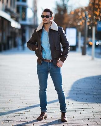 Wie kombinieren: dunkelbraune Leder Bomberjacke, hellblaues Jeanshemd, blaue enge Jeans, braune Lederfreizeitstiefel